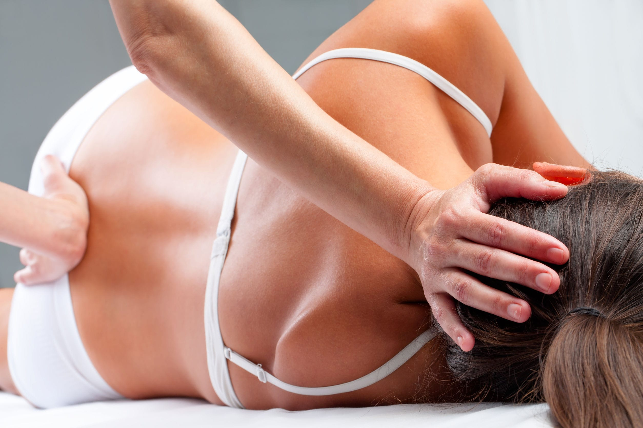 41985165 - close up of osteopath doing spinal column rehabilitation exercise on young woman.